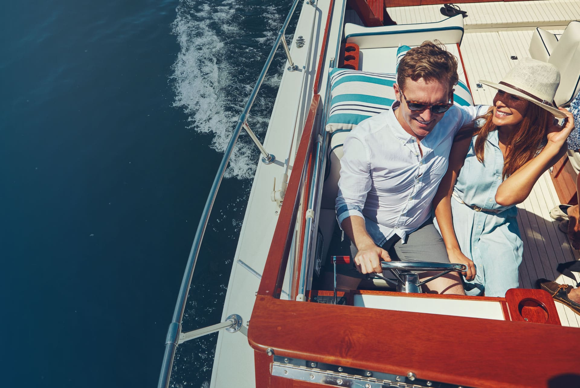 Man and woman driving a boat with mahogany trim and chrome railing.