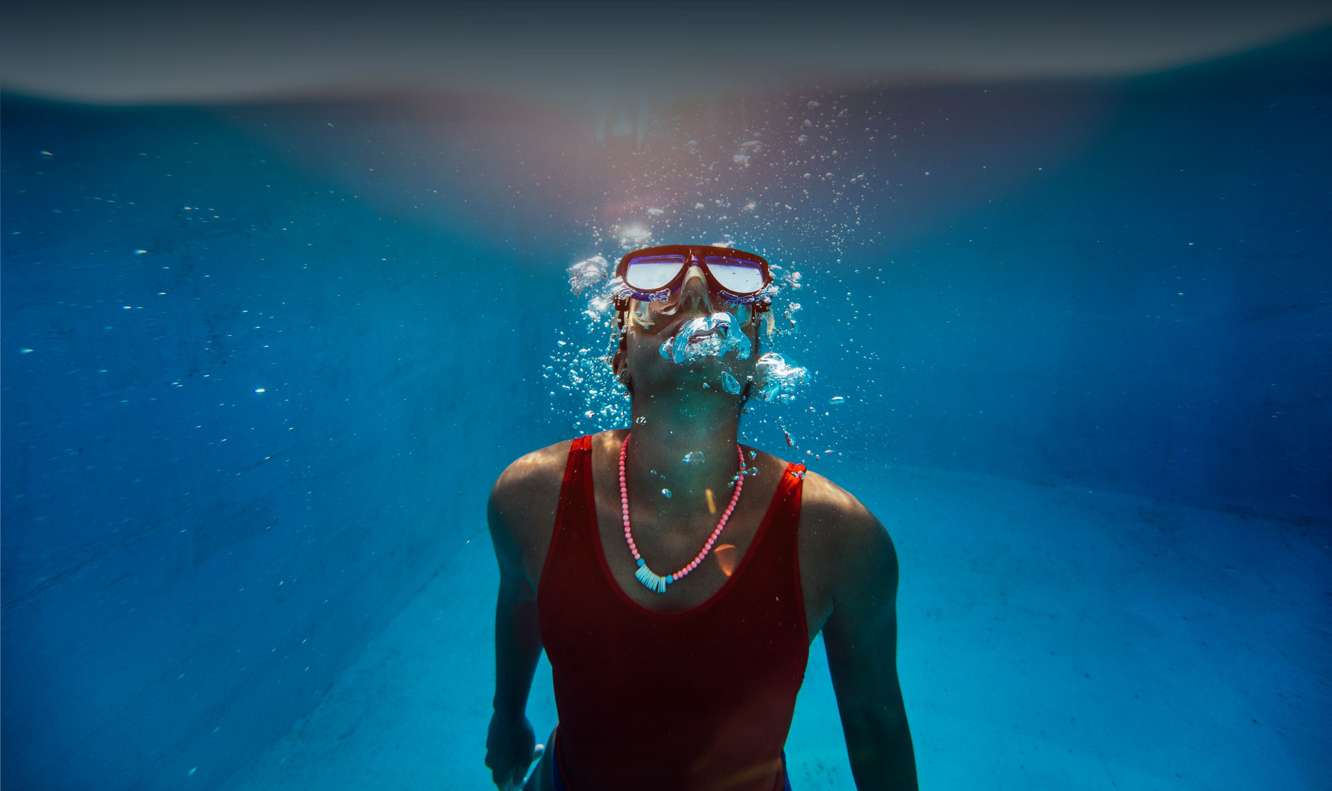Woman wearing a scuba mask swimming to the surface of a pool while blowing bubbles.