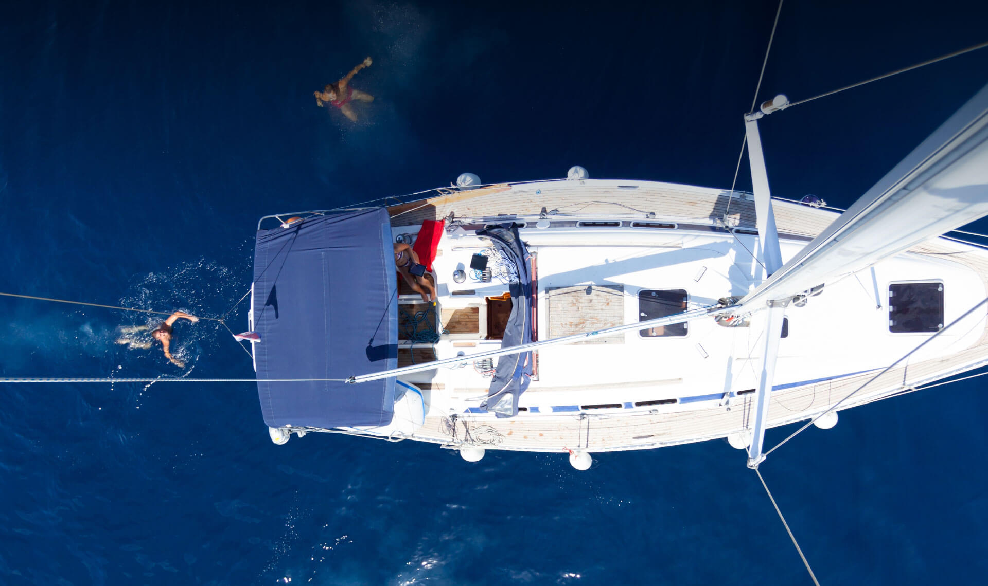 Bird's eye view of people swimming around a sailboat.