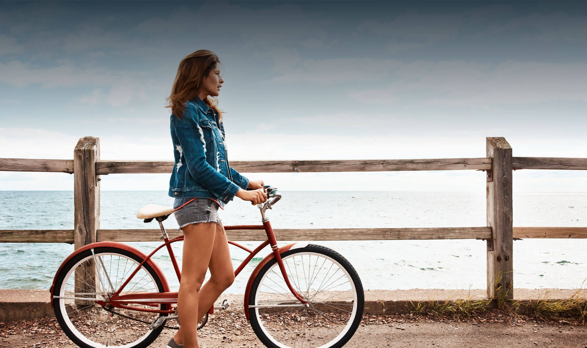 Woman standing next to a cruise bicycle looking at the ocean.